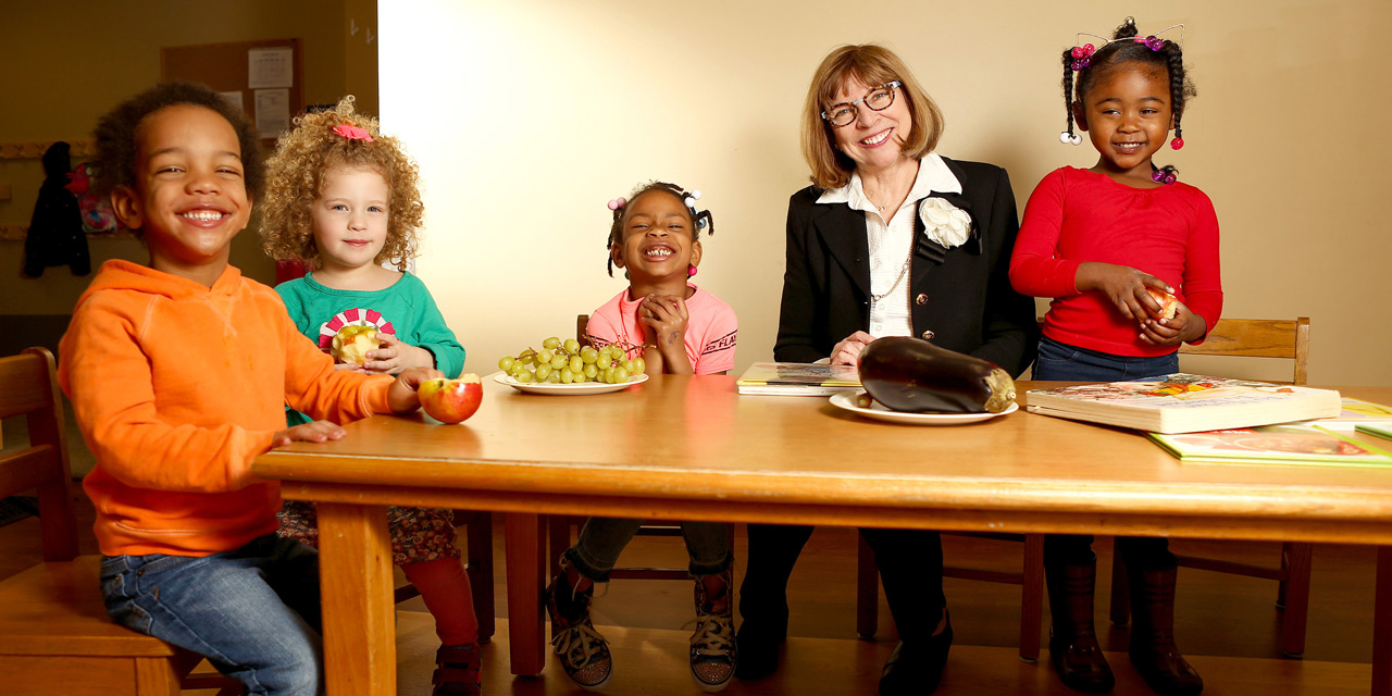 Woman teaches four children about nutrition at table with fruits and vegetables on it