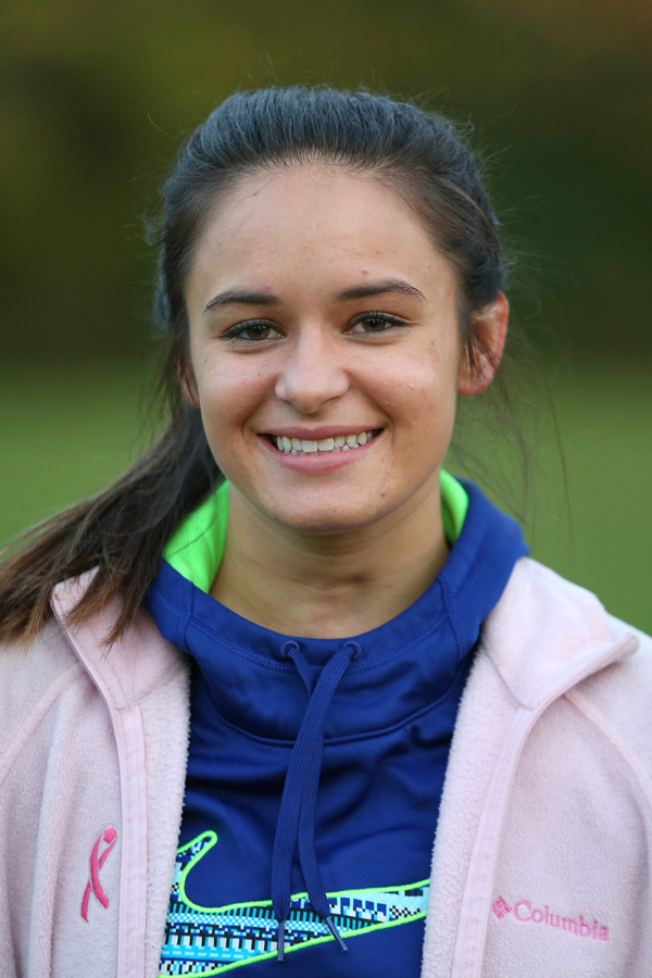 Portrait of young woman wearing pink coat and blue and green sweatshirt