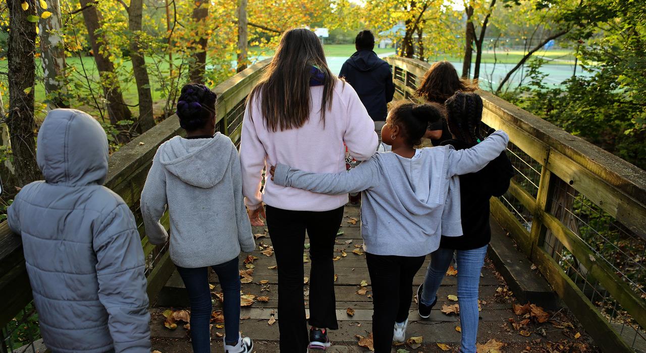 Young girl walks across bridge with boys and girls
