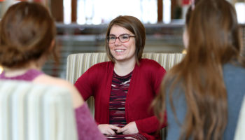 Woman in glasses and red sweater talk to two other women in Ohio Union