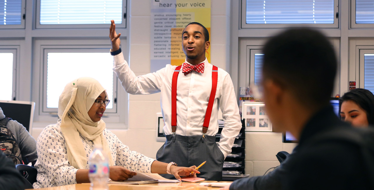Man in bow tie lectures to college students