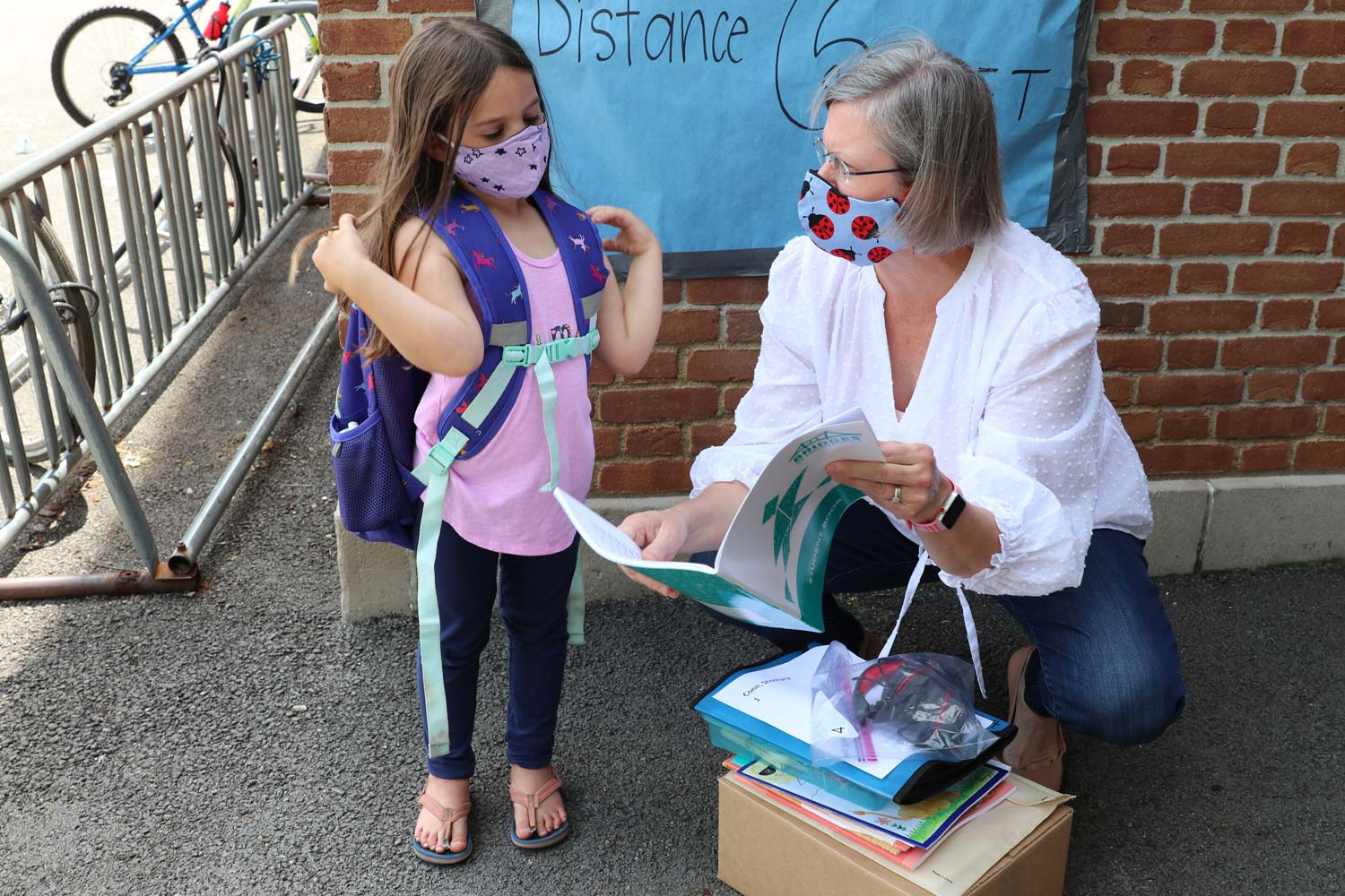 A crouching woman in a ladybug face mask talks with a young girl wearing a purple backpack and purple facemask about her school materials