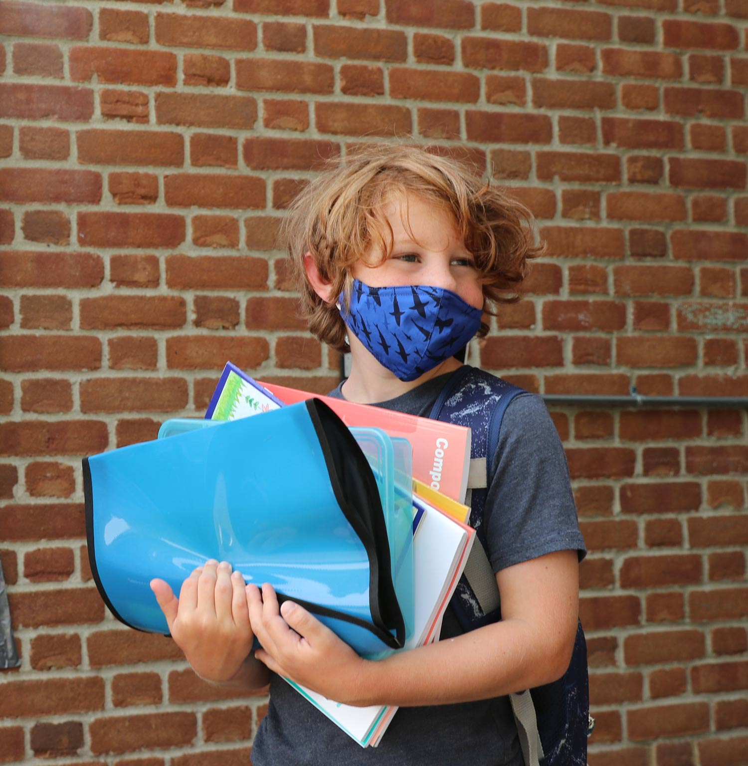 A boy in a blue, shark print face mask has his arms overflowing with supplies for the new school year