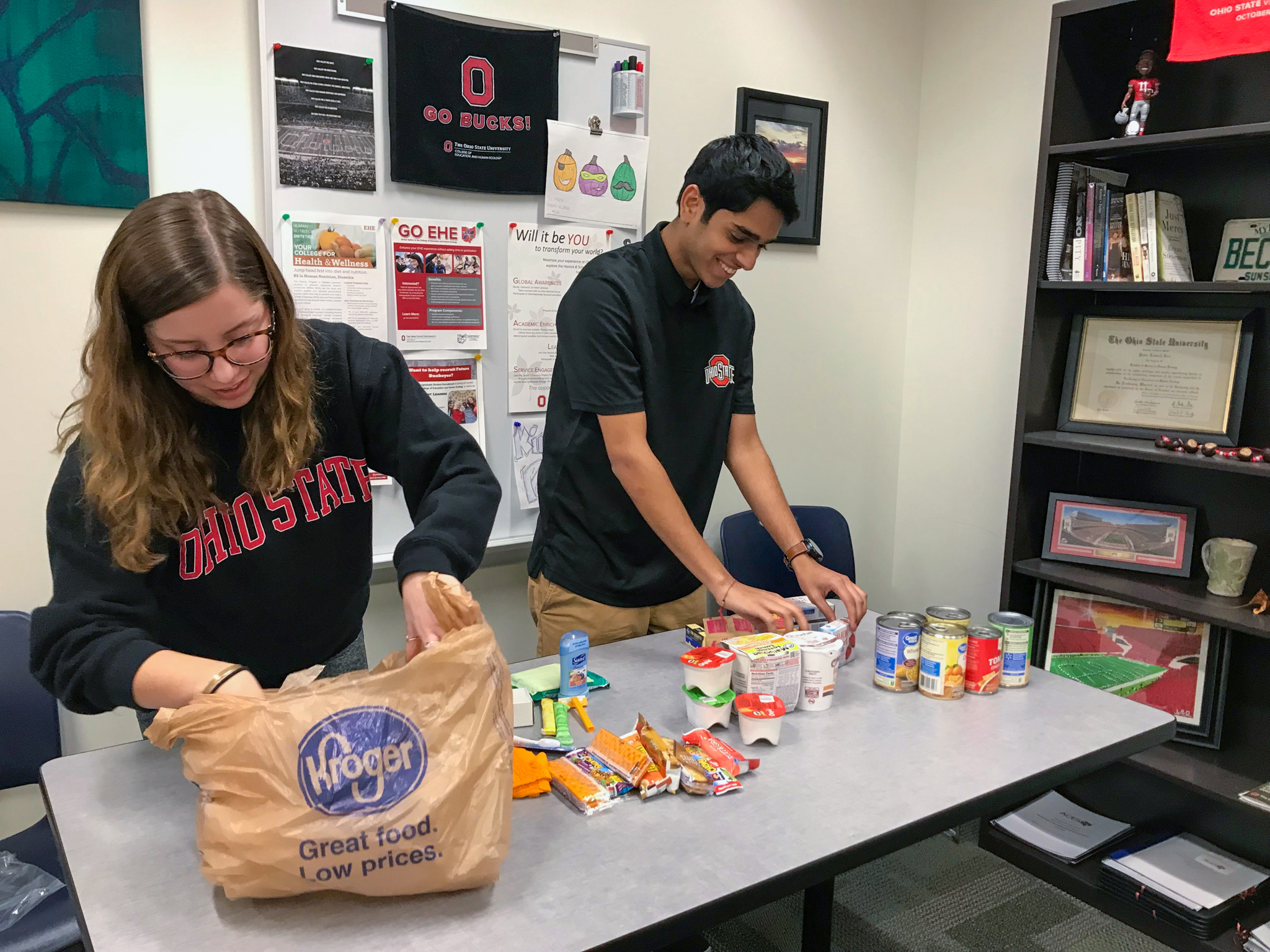 Two Ohio State students arrange food on a table for the college's food pantry