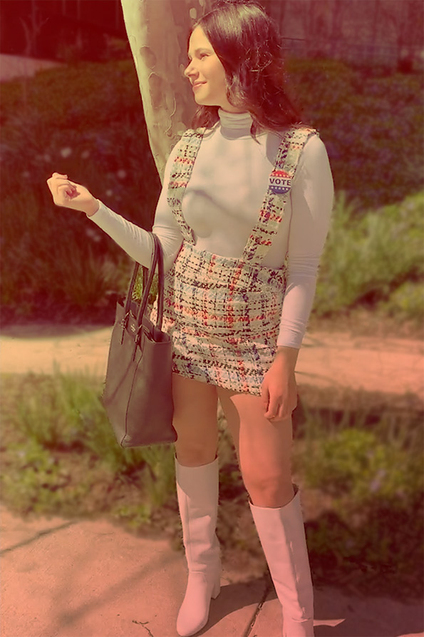 A woman models a long-sleeve white turtle neck, patterned overalls skirt, white knee-high boots and handbag
