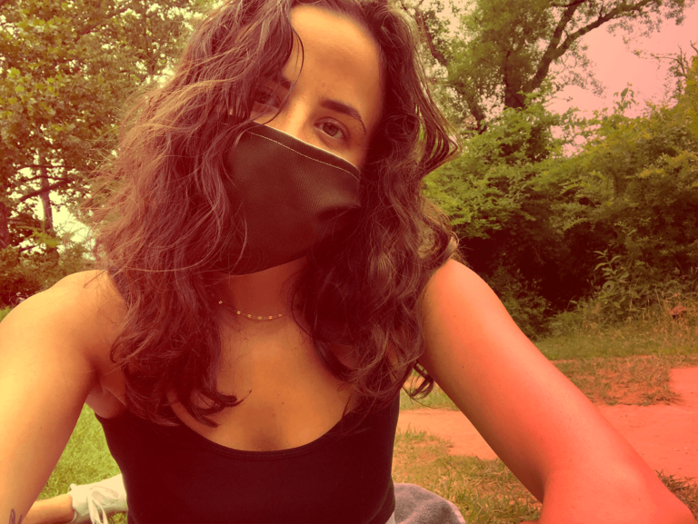 Selfie of a curly brown-haired woman wearing a dark green face mask