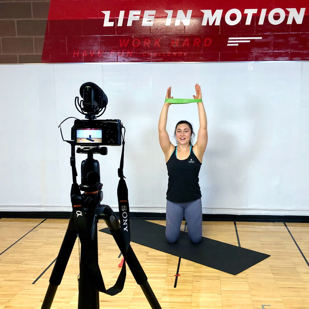 Fitness instructor records workout using resistance bands