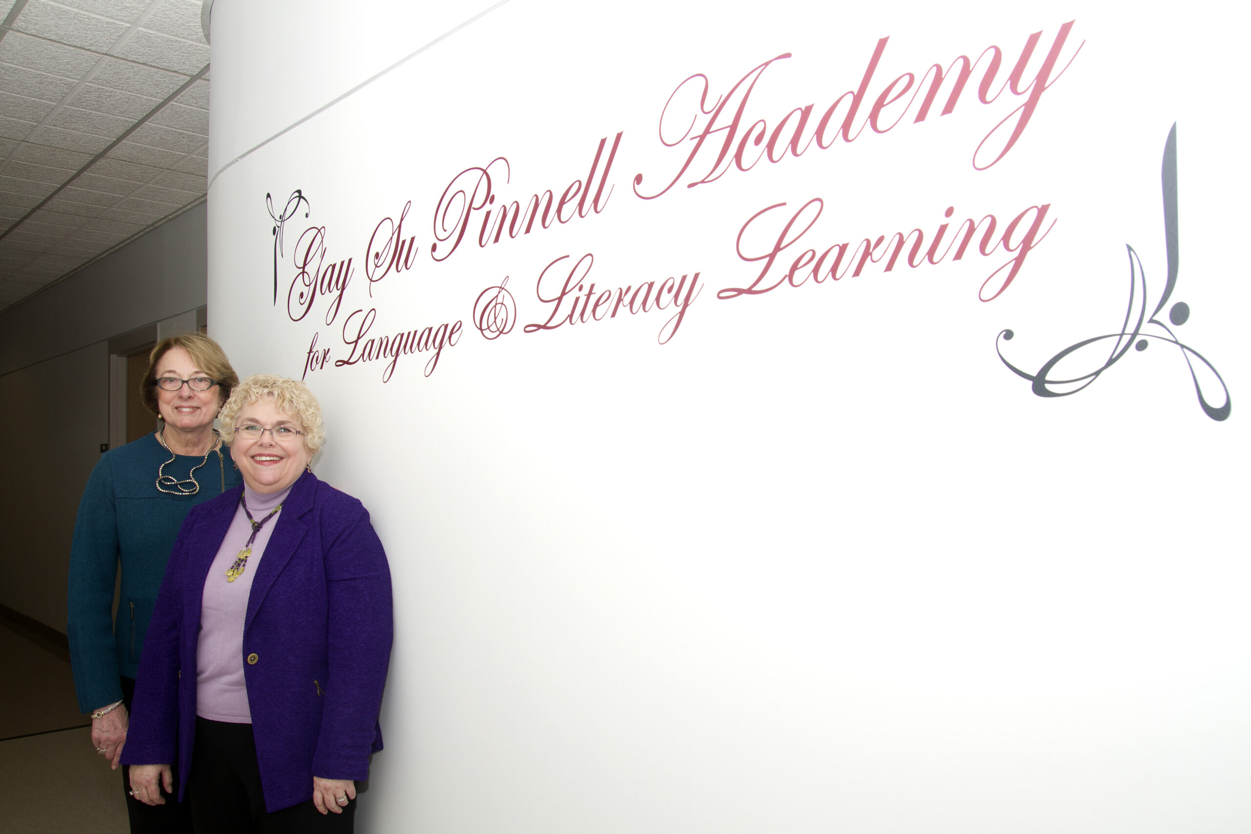 """Two women stand near a wall with writing that says """"Gay Su Pinnell Academy for Language and Literacy Learning"""""""